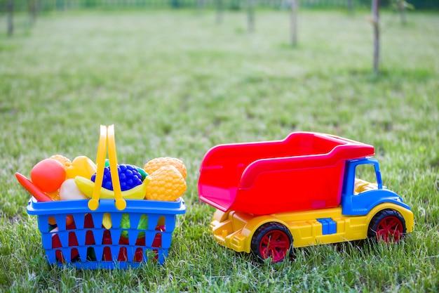 Автомобиль грузовик и корзина с игрушечными фруктами и овощами. яркие пластиковые красочные игрушки для детей на улице в солнечный летний день.