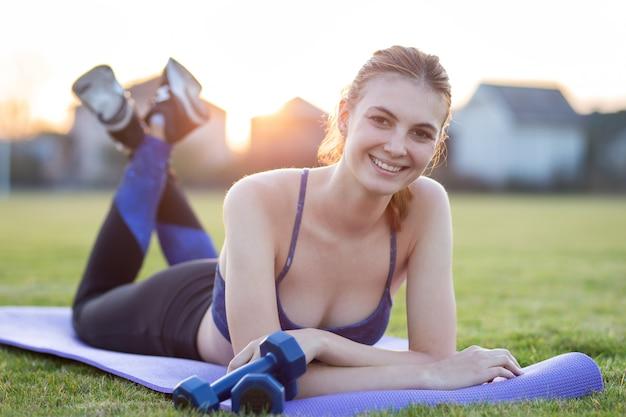 日の出フィールドで演習を行う前にトレーニングマットを置くスポーツ服の若い陽気な女性。