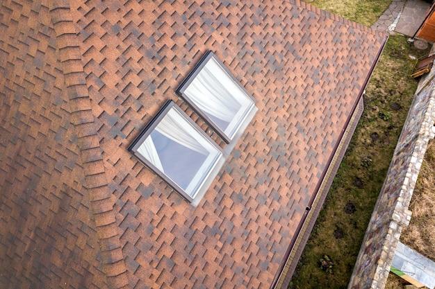屋根裏部屋のプラスチック窓は茶色の屋根のある家のルーに設置されています。