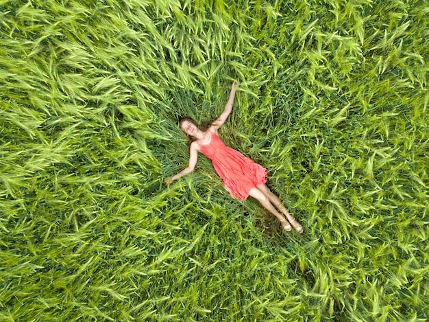 Женщина в красном платье лежит на зеленом пшеничном поле