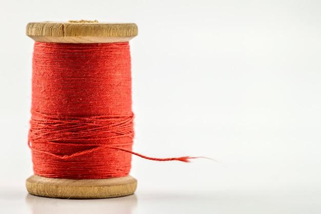 リールまたは白で隔離赤いミシン糸のスプール。被写界深度が浅い。クローズアップマクロ撮影。