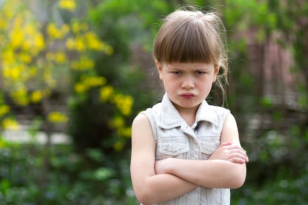 白いノースリーブのドレスを着たかなり面白い不機嫌そうな小さな金髪の就学前の女の子は、ぼやけた夏の背景に怒りと不満を感じてカメラに見えます。
