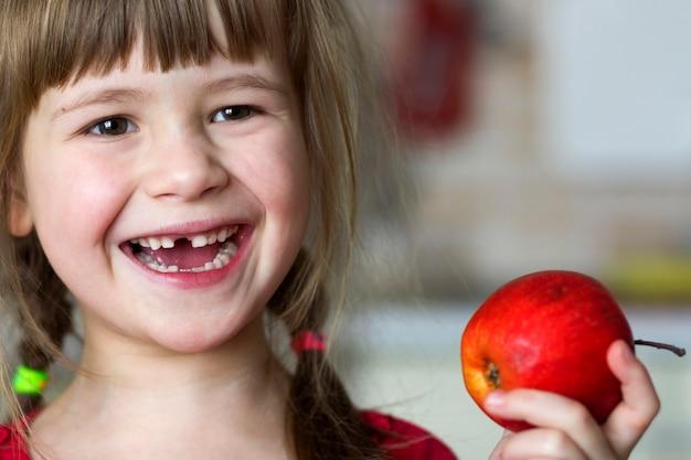 かわいい小さな巻き毛の歯のない少女は笑顔で赤いリンゴを保持しています。