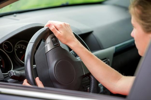 車のインテリア。ダッシュボードと女性は、車を運転するステアリングホイールに手します。