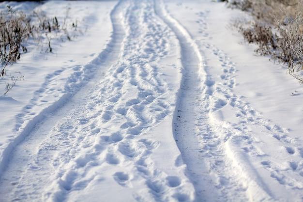 田舎、穏やかな冬の風景。車のタイヤ跡と空の見捨てられた道路上の人間の足跡