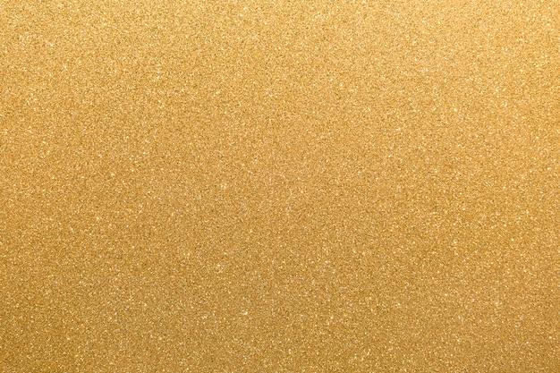 不規則な白い斑点の背景を点滅させる金色キラキラオレンジイエローの表面。