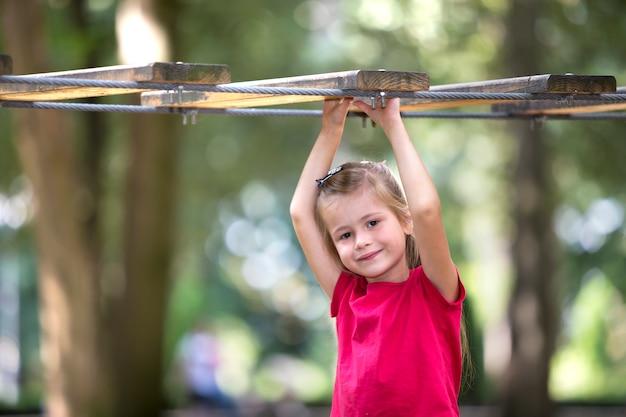 Портрет милой очаровательны улыбающегося белокурого ребенка девушка в летнем розовом платье с поднятыми руками, удерживая веревку путь на затуманенное зеленый солнечный свет боке. отдых и игры.