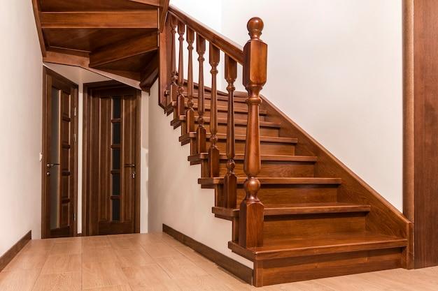 モダンな茶色のオークの木製の階段と新しい改装された家のインテリアのドア