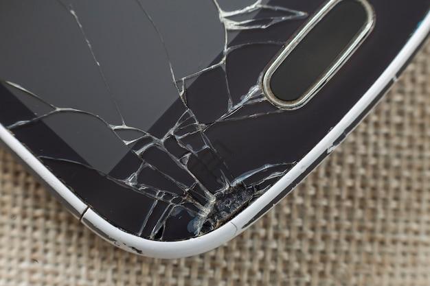 明るい布の背景にひびの入った画面と黒の古い携帯電話のクローズアップの詳細。ガジェットの修理およびメンテナンスのコンセプト。