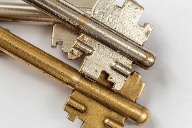 ステンレスと黄色の白い背景で隔離の古い金属製キーのクローズアップの詳細。安全性とセキュリティの概念。