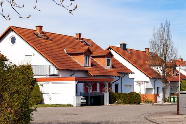 Классические немецкие жилые дома с оранжевой черепицей и окнами