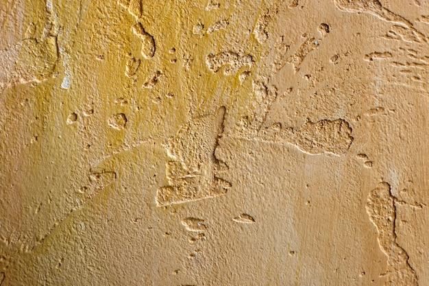 Конец-вверх красочной золотой бронзы заштукатурил неровную стену штукатурки. абстрактная текстура, хаотическая копия космический фон. декоративный гранж пространство.