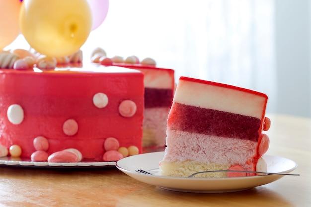 Домашний красный день рождения торт с воздушными шарами. ломтик красного бархатного торта на тарелку.