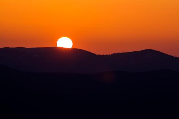 山の美しい夕日。夕日や日の出の暗い山の範囲の風景の劇的なオレンジ色の空に大きな明るい白い太陽の広いパノラマビュー。自然概念の美しさ。