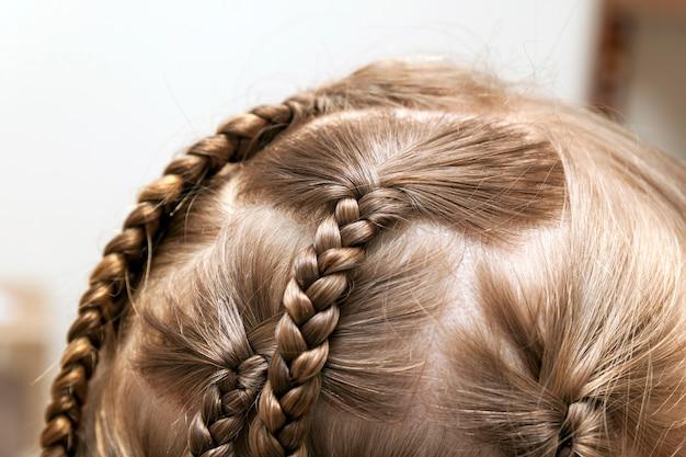 小さな女の子の三つ編みの髪のクローズアップ