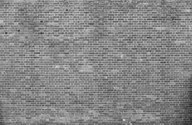 自然な古いヴィンテージ風化灰色の固体レンガの壁