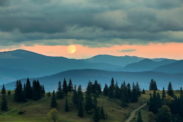 Покрытый туманом горы на рассвете, большая луна на ярко-оранжевом небе над высоким