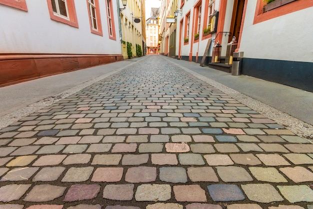 歴史的な伝統的な家屋とヨーロッパの古い町の青い空と夏の雲と石畳の通りの風光明媚な狭い通りの美しい景色