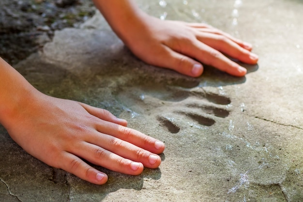 Детская рука и запоминающийся отпечаток руки в бетоне