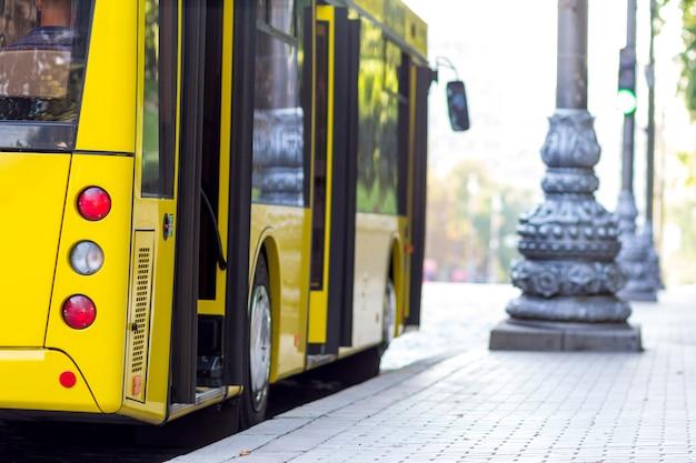バスの駅で開いているドアとモダンな黄色の市バス