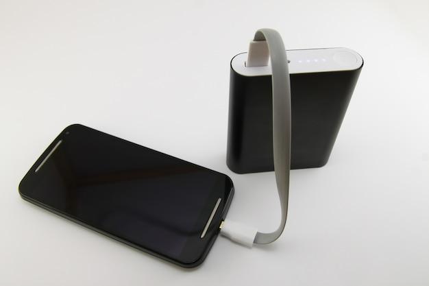 白で隔離されるブラックパワーバンクから充電するスマートフォン。スマートフォンとパワーバンクのコンセプト。