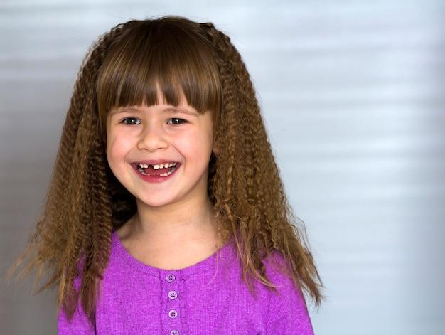美しい太い髪を持つ幸せな笑みを浮かべて少女の肖像画