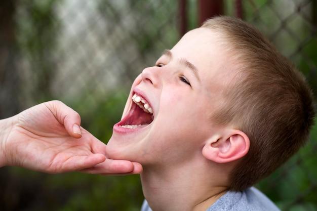母親は、彼の白い面白い子供の歯を屋外に示す小さな笑みを浮かべてハンサムな少年のあごを愛情を込めて保持します。幸せな家族関係、医療、歯科問題の概念。