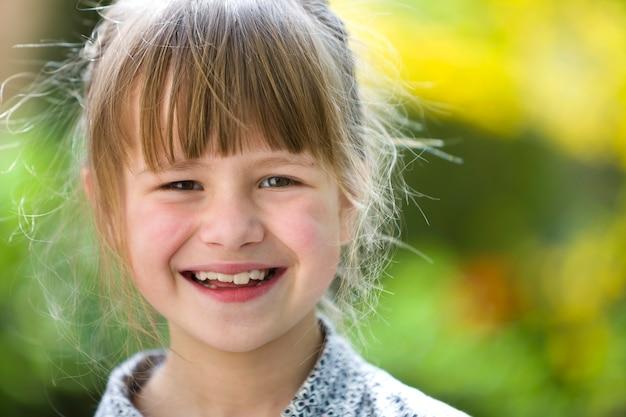 灰色の目とぼやけた日当たりの良い緑と黄色の明るいボケ自然に屋外カメラで笑顔金髪のかわいい美少女