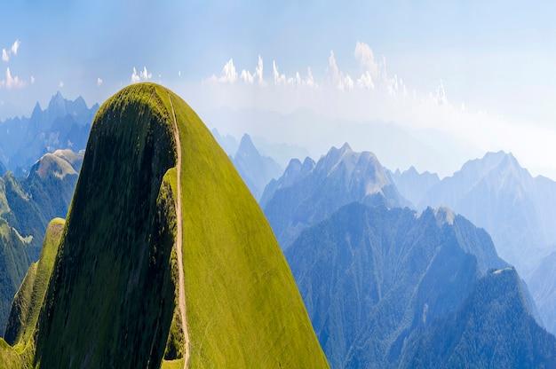 車で旅行するための砂利道と夏の山の緑の丘のパノラマ