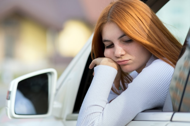 Грустно женщина водитель, глядя из окна автомобиля.