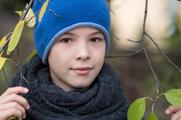 寒い屋外で緑の葉と木の枝を保持している暖かい冬の服を着てかわいい子少年。