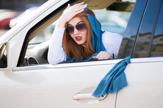 若いファッショナブルな女性ドライバーは、彼女のスカーフが車のドアに詰まっているとそれを引き出しています。