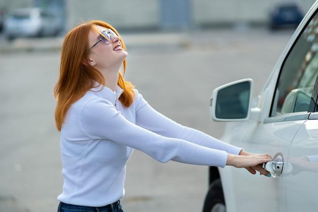 閉じた車のドアを開こうとしている女性。