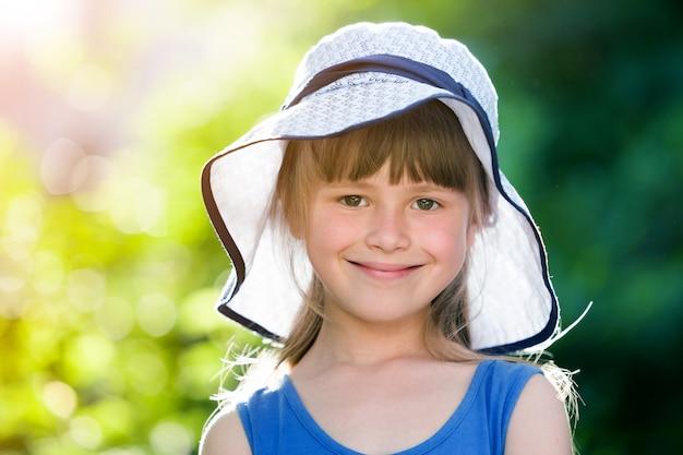 大きな帽子で幸せな笑みを浮かべて少女のクローズアップの肖像画。夏の屋外の時間を楽しんでいる子。