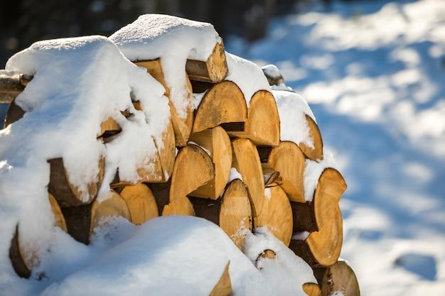 明るい寒い冬の晴れた日に屋外で雪で覆われたみじん切りの乾燥したトランクの木のきちんと積み重ねられたスタック