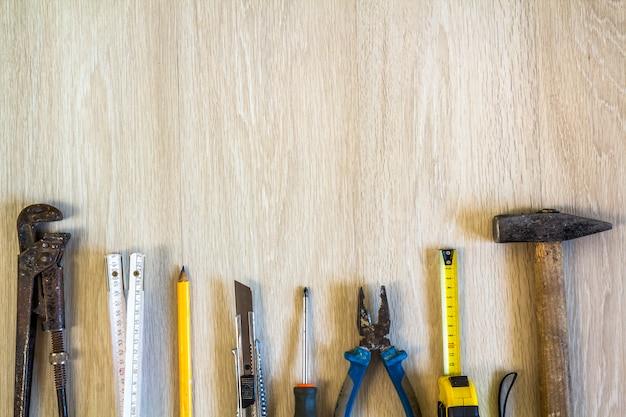 Инструменты конструкции, здания и ремонта установили для работы дома на деревянной предпосылке. вид сверху.