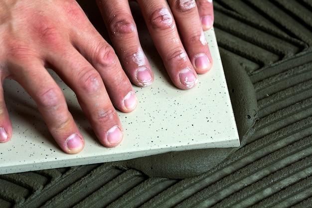 セラミックタイルと瓦職人のためのツール。床タイルをインストールする労働者の手。改築、改修-セラミックタイルの床の接着剤、モルタル、レベル。