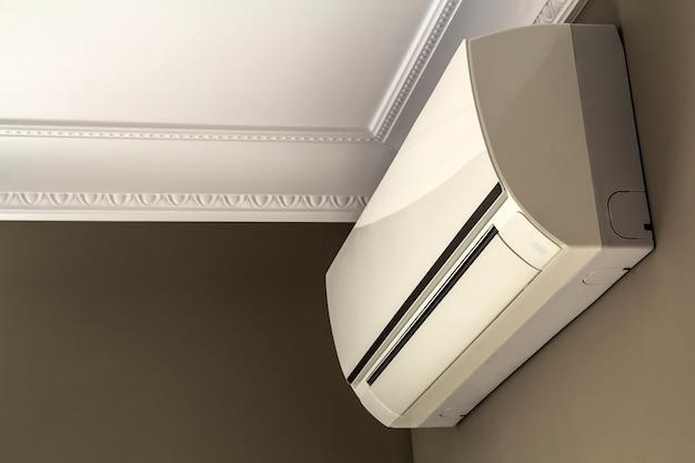 Прохладная система кондиционирования на темной стене в интерьере комнаты
