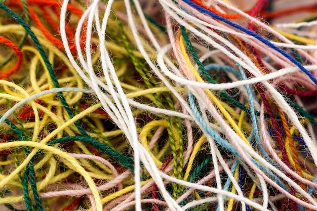 マルチカラーのもつれたカラフルなニードルクラフトシルクスレッドロープ。マクロ撮影。抽象的な色の背景