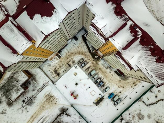 Воздушное зимнее вид сверху современного большого жилого дома в пригородной зоне на узкой грязной дороге и снежном поле.