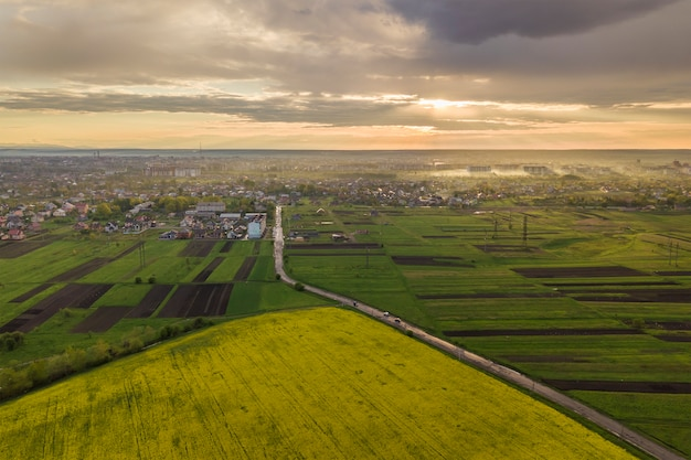 春または夏の日の田園風景。緑、耕した、咲くフィールド、家の屋根、晴れた夜明けの道の空撮。ドローン写真。