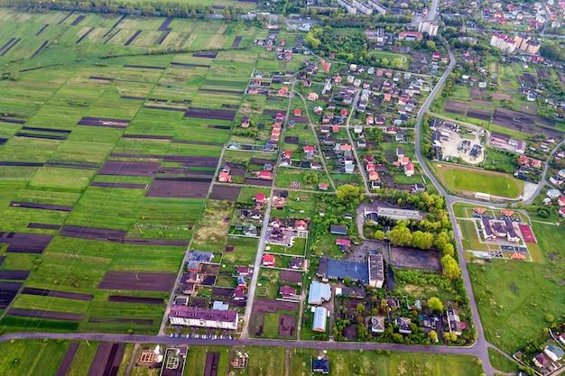 春または夏の日の田園風景。日当たりの良い夜明けの緑と耕した畑、村や町の家の屋根と道路の空撮。ドローン写真。
