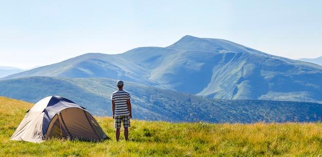 カルパティア山脈のキャンプテントの近くに立っているハイカーの男。観光客は山の景色を楽しみます。旅行のコンセプト。