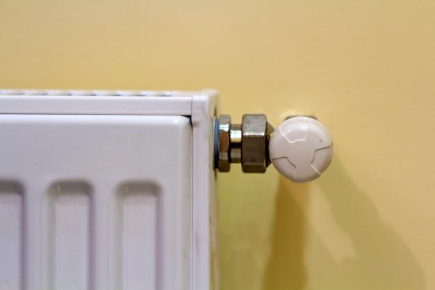 Конец-вверх белого радиатора отопления с клапаном термостата на светлой предпосылке космоса экземпляра стены. удобный теплый домашний интерьер, климат-контроль, концепция экономии денег.