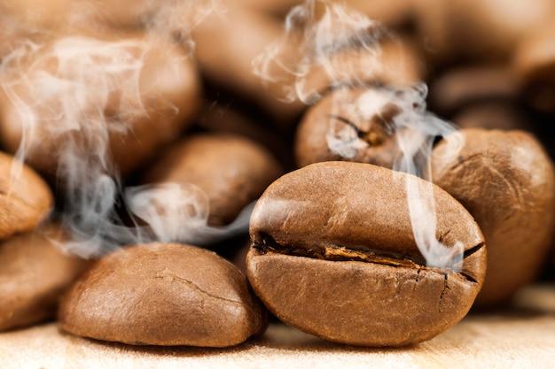 黄色のテクスチャ木製ボード上の白い煙蒸気と茶色のコーヒー豆