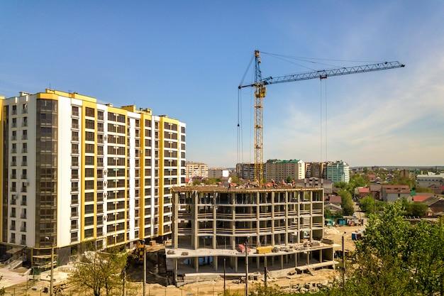 建設中のアパートまたはオフィスの高層ビル。働くビルダーとタワークレーン