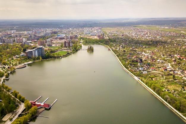 Вид с воздуха городского озера среди зеленых деревьев и зданий города в зоне парка отдыха. беспилотная фотография.