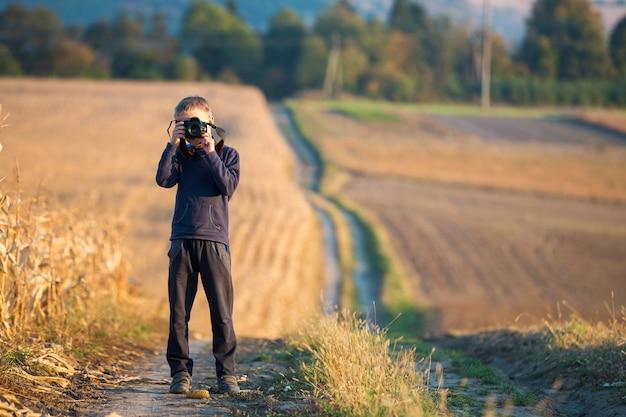 Мальчик маленького ребенка с фотоаппаратом фотографируя поле пшеницы