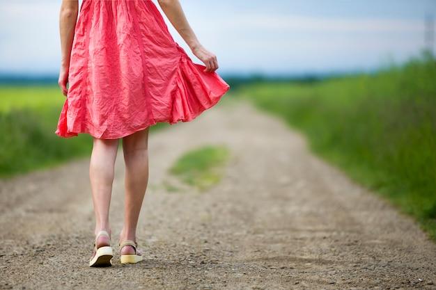 日当たりの良い背景をぼかした写真の夏の日に地面の道を歩いて赤いドレスの足の若い女性の背面図。
