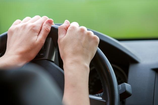 女性は車を運転してステアリングホイールに手します。